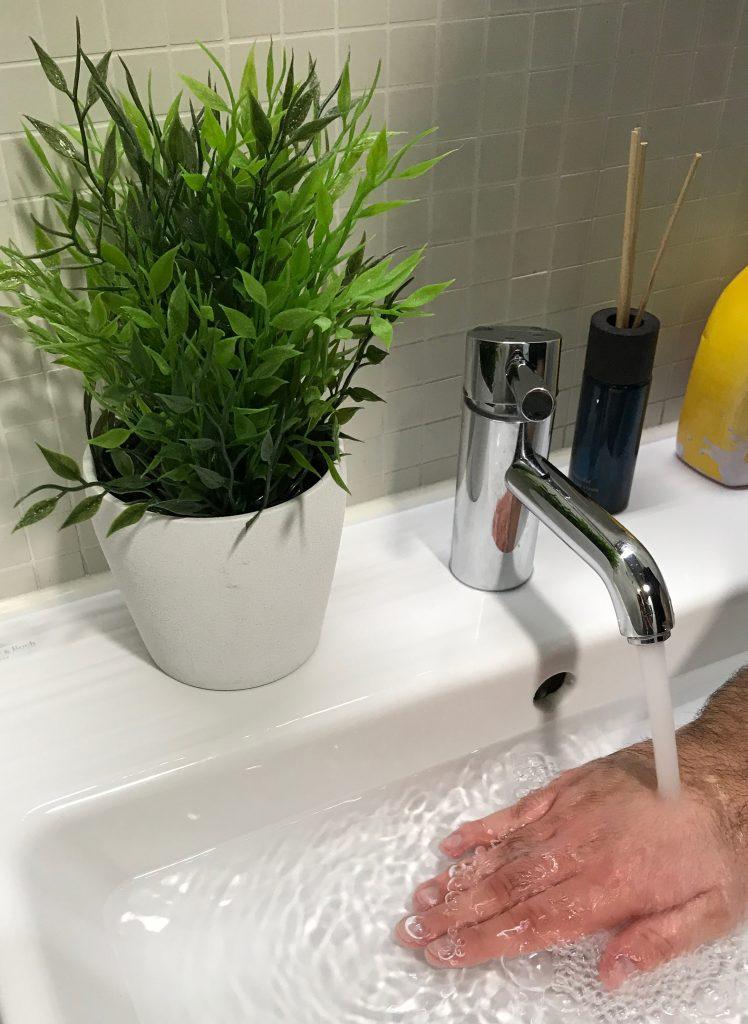 Person hält Hand unter laufendes, warmes Wasser.